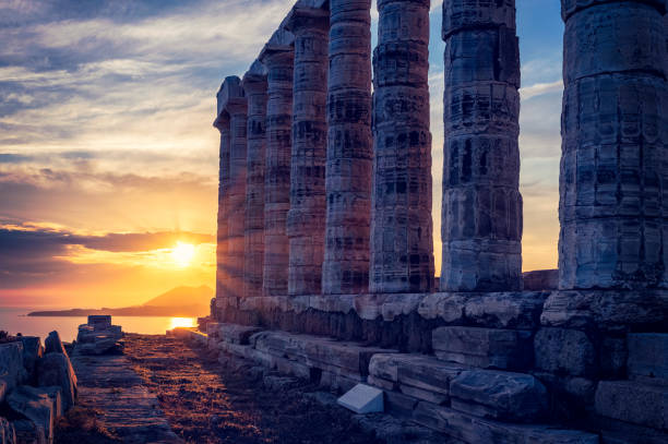 Poseidon temple ruins on Cape Sounio on sunset, Greece Greece Cape Sounio. Ruins of an ancient temple of Poseidon, Greek god of the sea, on sunset. Shot of temple ruins on sunset. Tourist landmark of Attica, Sounion, Greece headland stock pictures, royalty-free photos & images