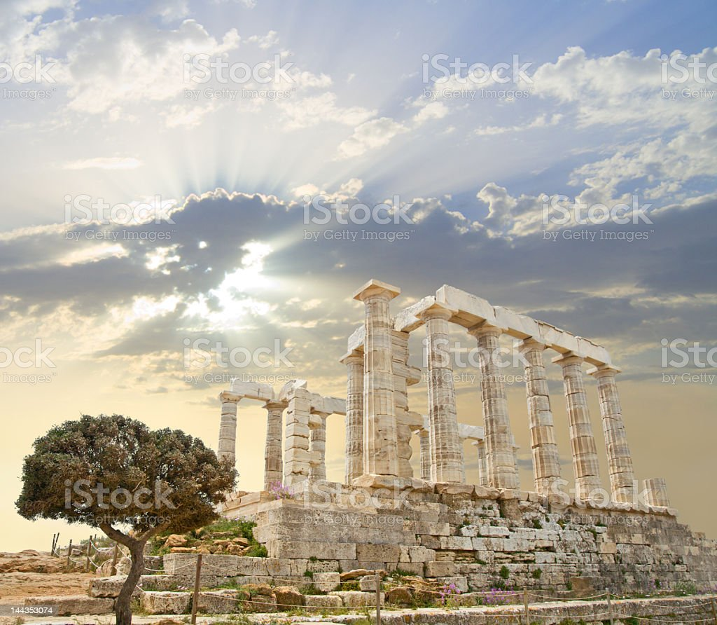 Poseidon's Temple in Greece with the sun behind the clouds stock photo