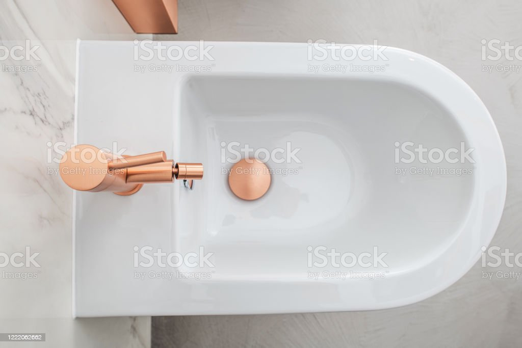 Posh White Bidet With Copper Fixture. Luxurious Whote Bidet With Copper Fixture In Marble Tile Bathroom. Bathroom Stock Photo