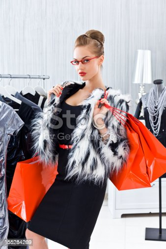 Portrait of elegant young adult woman wearing a fur jacket and black dress posing in luxury boutique with red shopping bags.