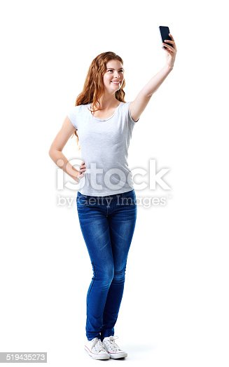 Studio shot of an attractive young woman taking a selfie with her mobile phone
