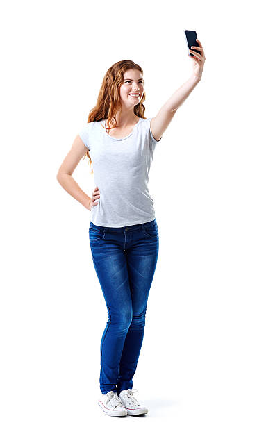 Posing for a casual selfie Studio shot of an attractive young woman taking a selfie with her mobile phone skinny jeans stock pictures, royalty-free photos & images