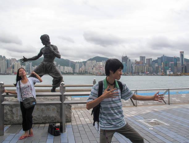 Posando em frente à estátua do Bruce Lee, Hong Kong, China - foto de acervo