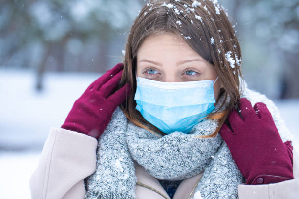 Posing on the snow with protective mask stock photo