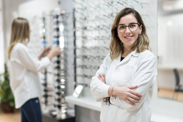Posing optometrist woman in eyeglasses store smiling looking at camera Posing optometrist woman in eyeglasses store smiling looking at camera optometrist stock pictures, royalty-free photos & images