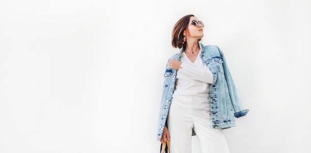 Posierende Frau in elegantem weißen Outfit mit oversize Jeansjacke – Foto
