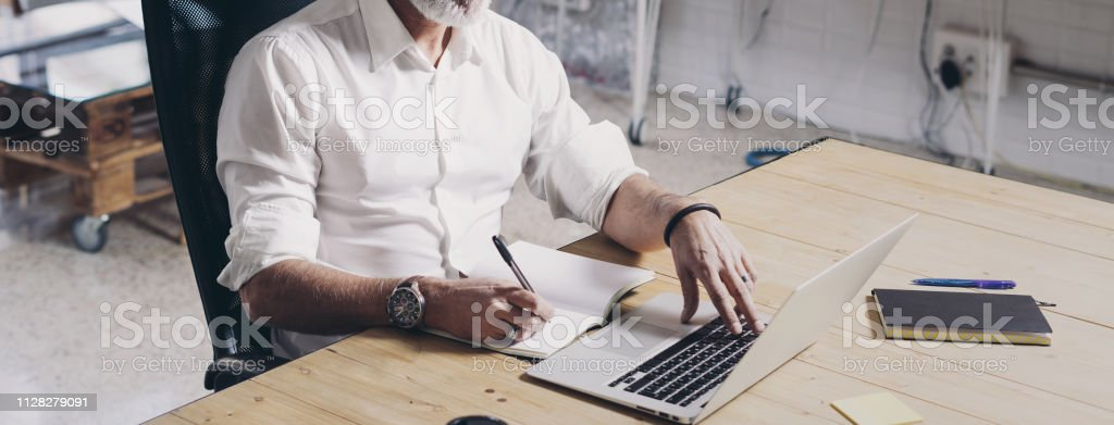 Positive Adult businessman using mobile laptop computer while sitting at wooden table at modern coworking place. Wide. Cropped. stock photo