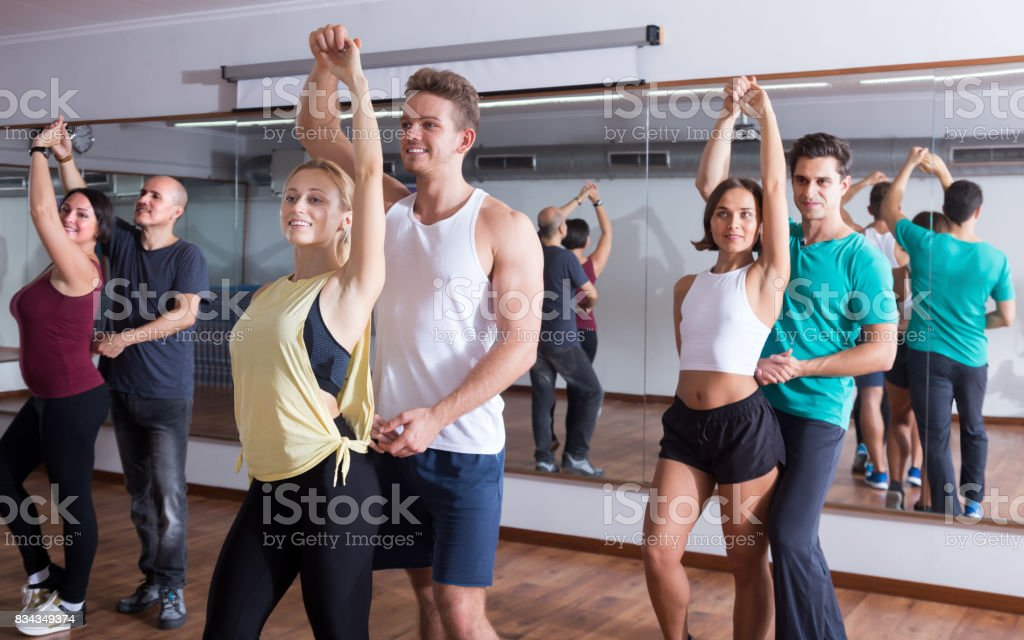 Positive adults dancing bachata together stock photo