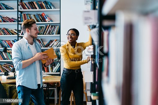 istock Positive african american female librarian helping caucasian student to search literature book in bookshelf.Cheerful two young people in casual wear discussing new bestseller standing in library 1168056915