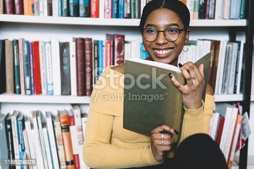 Positive african american young woman in eyeglasses for vision correction laughing while looking away and holding book in hands.Cheerful dark skinned student enjoying literature plot from bestseller