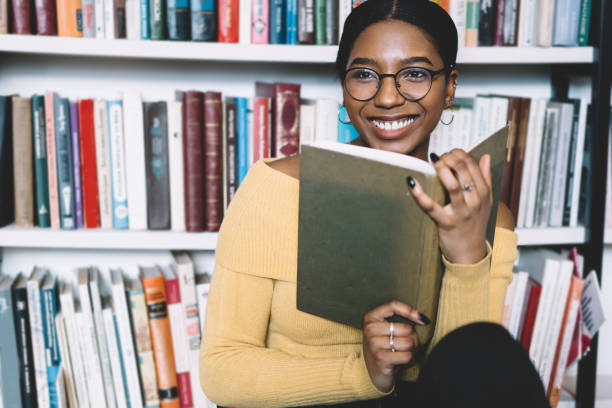 Positive african american young woman in eyeglasses for vision correction laughing while looking away and holding book in hands.Cheerful dark skinned student enjoying literature plot from bestseller stock photo