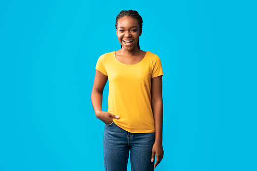 Positive African Girl In Braces Standing In Studio, Blue Background