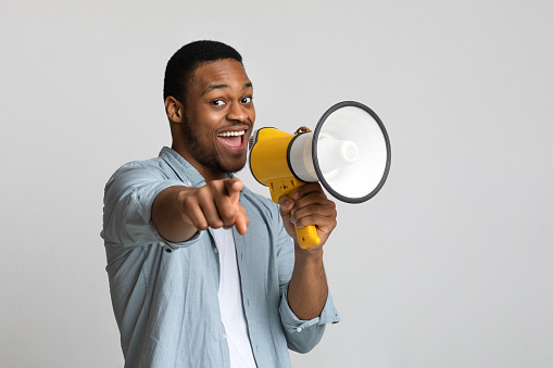 Positive african american guy shouting in megaphone and pointing at camera over grey background, copy space. Happy black man screaming with loudspeaker, cheering up, making advertisement