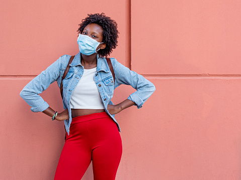 positive afro pretty girl, smile with the eyes and wearing protective and medical mask, white t-shirt and jeans jacket, red pant over pastel coral pink background