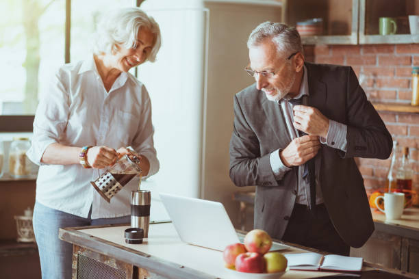 Positive aged couple standing in the kitchen stock photo