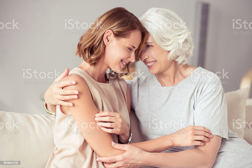Positive aged woman and her daughter embracing - foto de stock