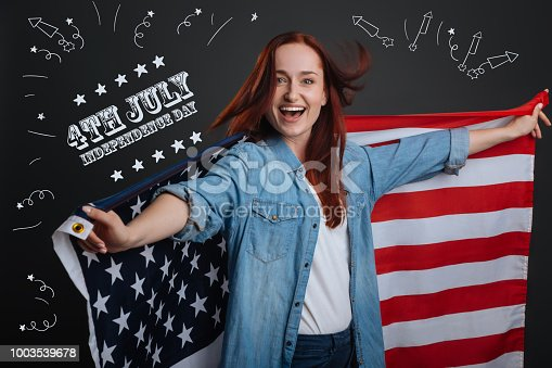 1003539592istockphoto Positive American citizen holdign a national flag 1003539678