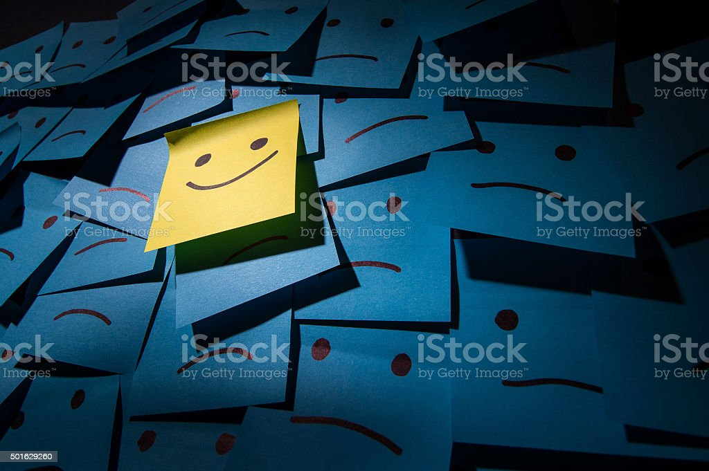 Positive and negative smiley Post it Yellow adhesive note stuck on the wall with funny smiley face 2015 Stock Photo