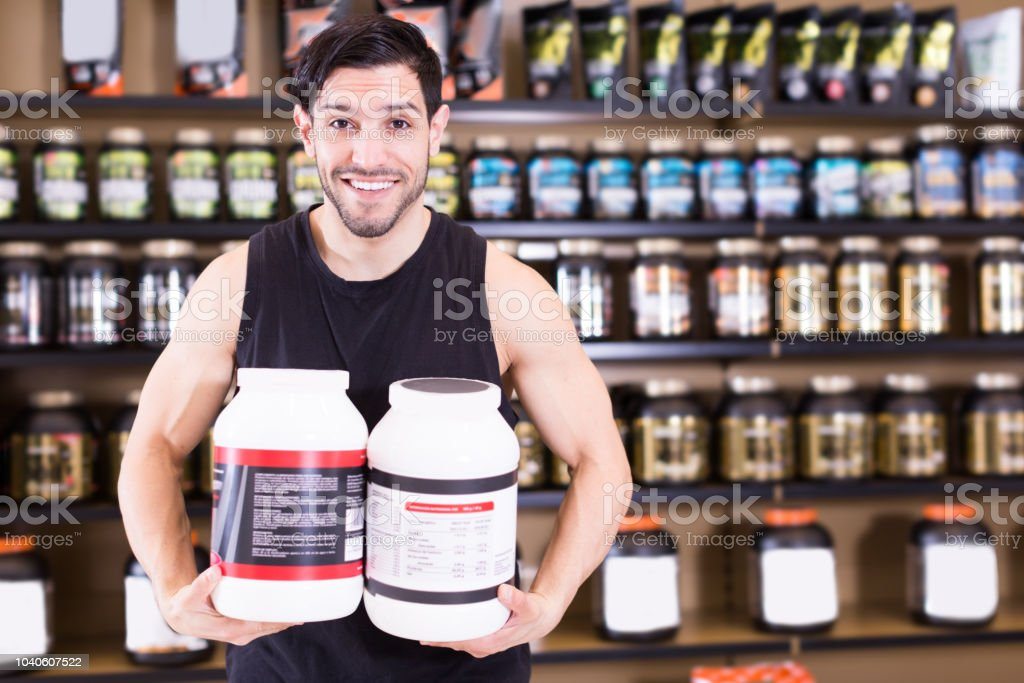 Positive athletic man seller  holding jars of sport supplements stock photo