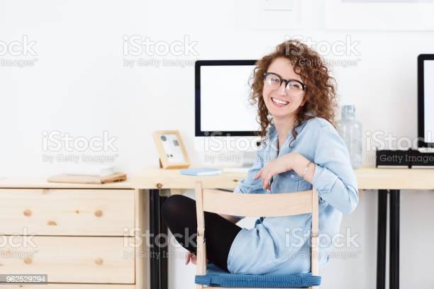 Foto de Positiva Atraente Feminino Estudante Americana Em Óculos Redondos Sorrindo Para A Câmera Desfrutando De Um Dia Produtivo Enquanto Está Sentado Na Frente Do Computador e mais fotos de stock de Adulto