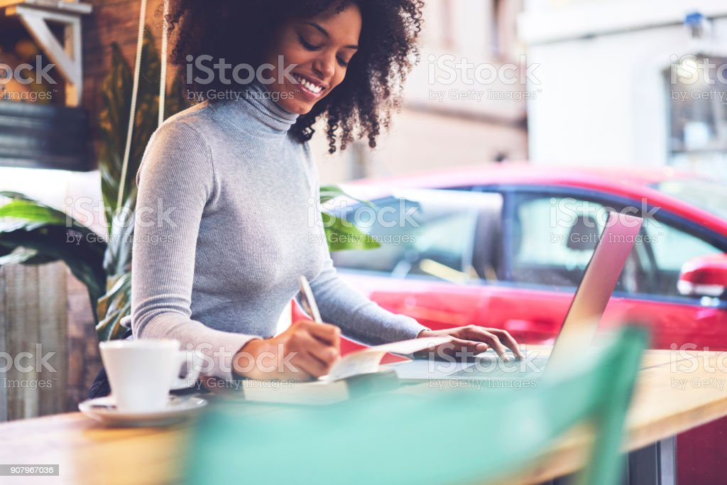 Positive attractive businesswoman dressed in stylish clothing planning working process using application on laptop connected to wireless internet and recording information in textbook sitting at table stock photo