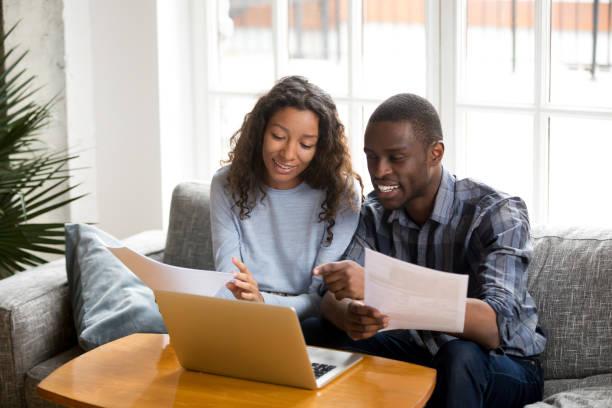 positive black couple with bills and laptop at home - кредит и кредитные карты стоковые фото и изображения