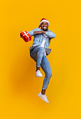 istock Positive black guy in Santa hat jumping with Xmas present 1187582695