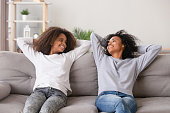 Happy african mother and teen daughter relaxing hold hands behind head sitting on sofa in living room, different ages sisters or adolescent and nanny spending time at home chatting breathing fresh air