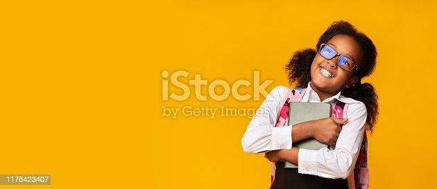 istock Positive Black Schoolgirl Embracing Book, Studio Shot, Panorama 1175423407