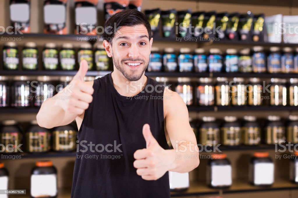 Positive bodybuilder  holding thumbs up in sport nutrition products store stock photo