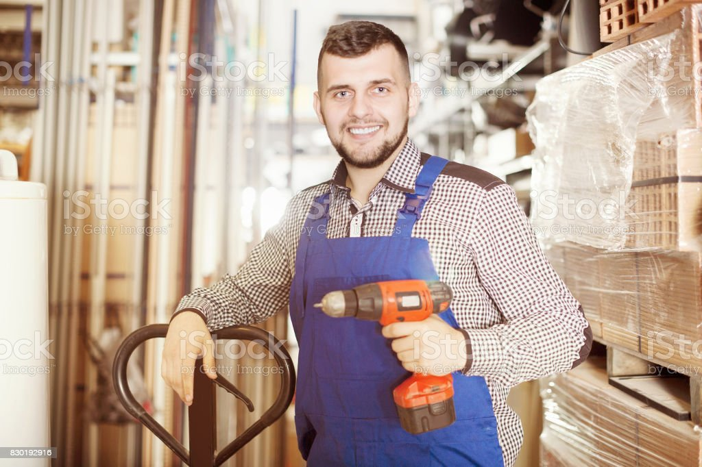 Positive builder male demonstrating various tools stock photo