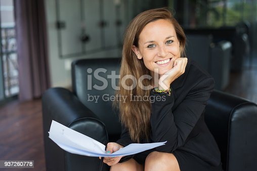 istock Positive Business Lady Holding Documents in Lobby 937260778
