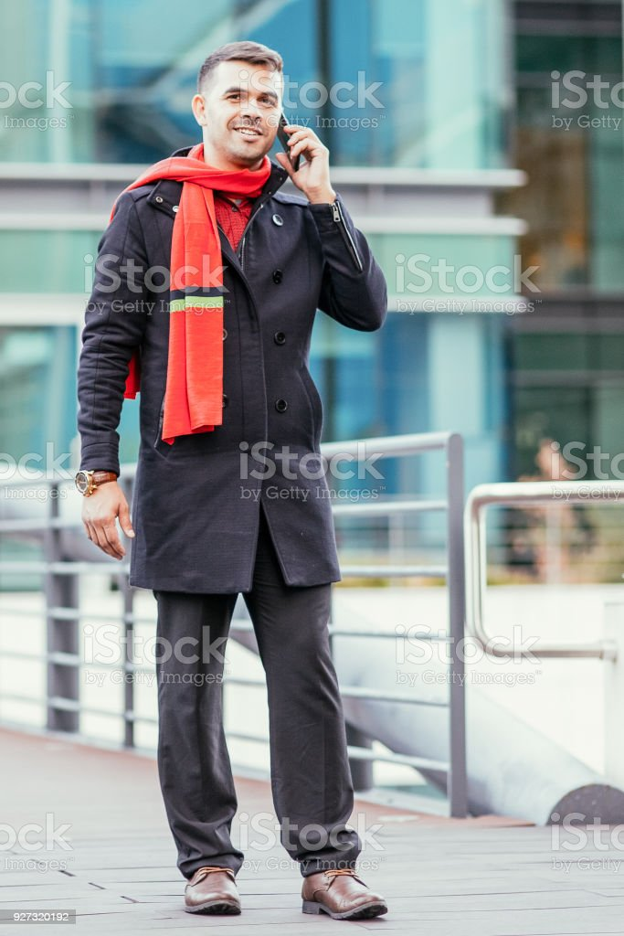Portrait of positive young Caucasian businessman wearing coat and...