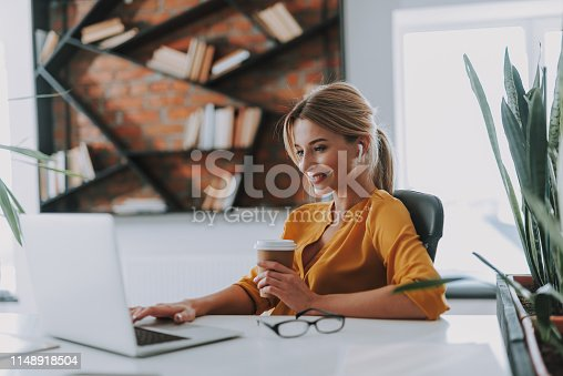 Blonde woman in an orange blouse having a carton cup of coffee in her hand and wearing wireless earphones while working on the laptop
