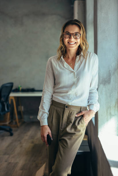 Positive businesswoman in office Positive businesswoman standing in office. Woman in casuals standing by window in office looking at camera. jacoblund stock pictures, royalty-free photos & images