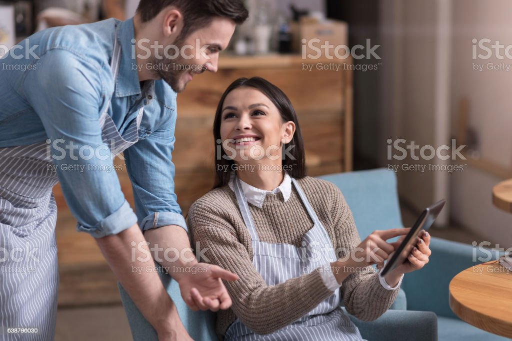 Positive cafe owners communicating stock photo