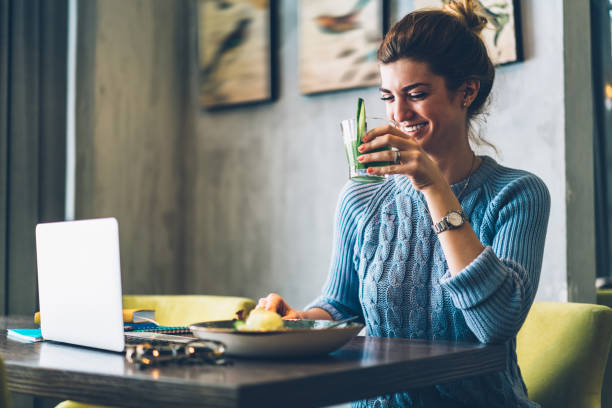 Positive caucasian young woman with tasty cocktail in hand laughing while sitting at table with modern laptop computer.Cheerful hipster girl drinking beverage having dinner in cafe stock photo