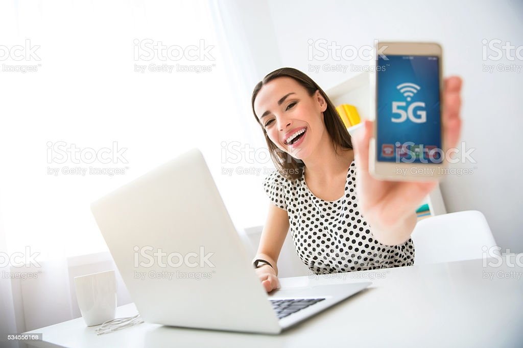 Positive charming woman holding cell phone stock photo