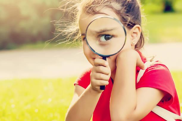 positiv glad liten flicka tittar genom ett förstoringsglas utomhus - investigating eye bildbanksfoton och bilder