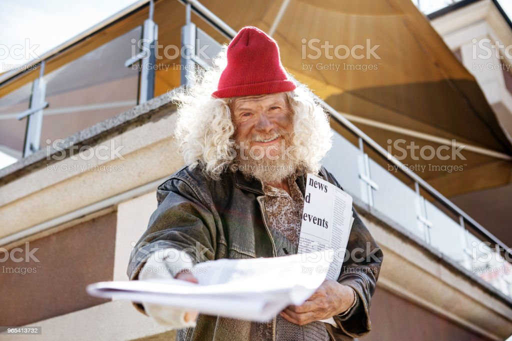 Positive cheerful man giving you a newspaper royalty-free stock photo