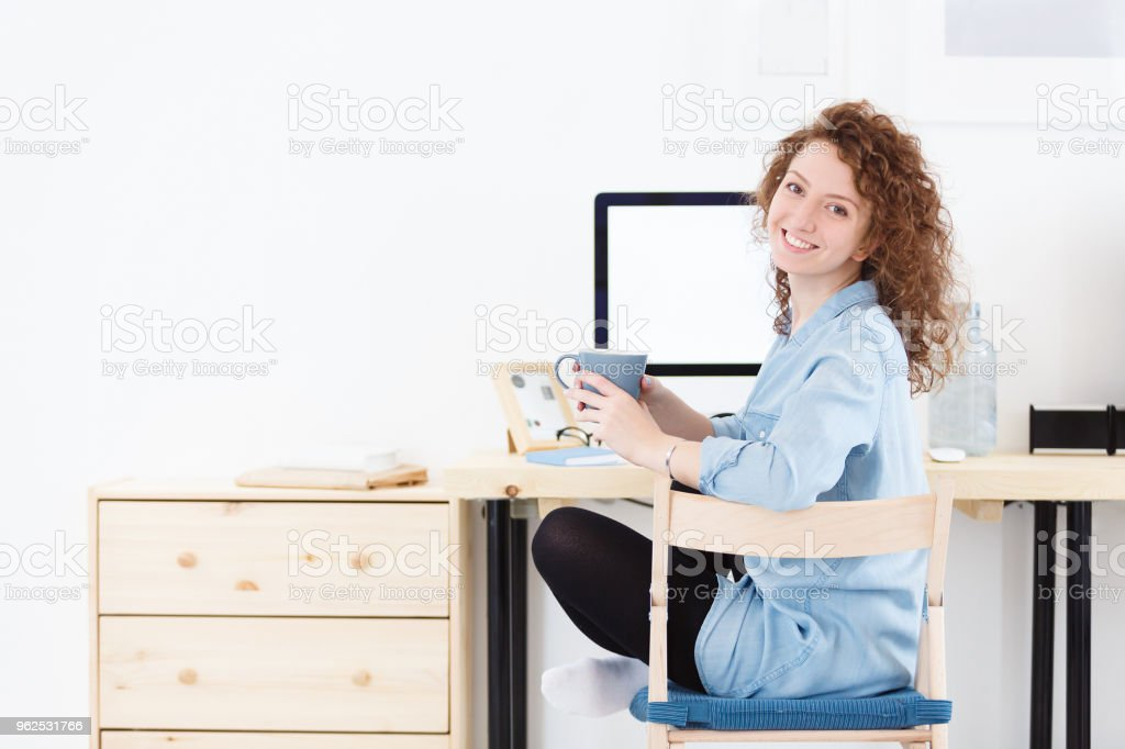 Positive cheerful young Caucasian female programmer or startupper looking and smiling at the camera during small break,downloads program at laptop computer - Royalty-free Adult Stock Photo