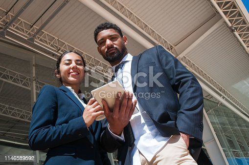 Positive colleagues posing, holding tablet and drink outdoors. Business man and woman looking at camera with building constructions in background. Business people concept. Low angle front view.