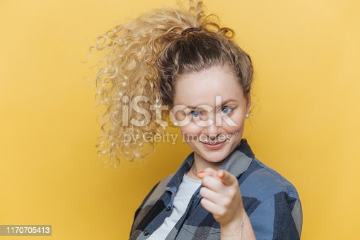 Positive confident beautiful female with curly pony tail, indicates directly at camera, chooses you, dressed in casual clothing, isolated over yellow background. Shot of pretty woman gestures indoor