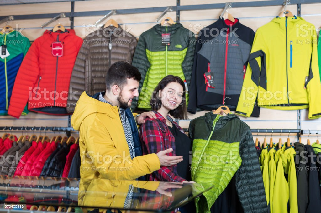 Positive couple deciding on windcheater in store stock photo