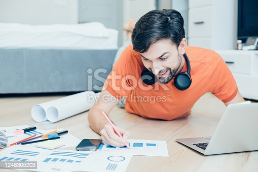 994789938 istock photo Positive creative man smiling and improving his project 1248305203