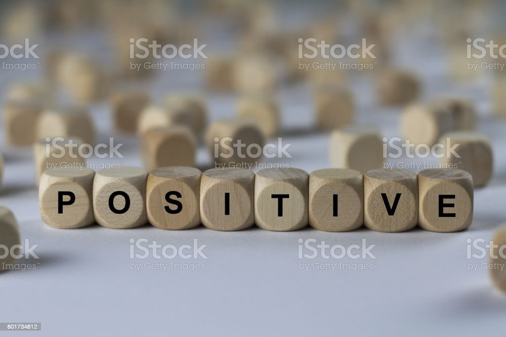 positive - cube with letters, sign with wooden cubes stock photo