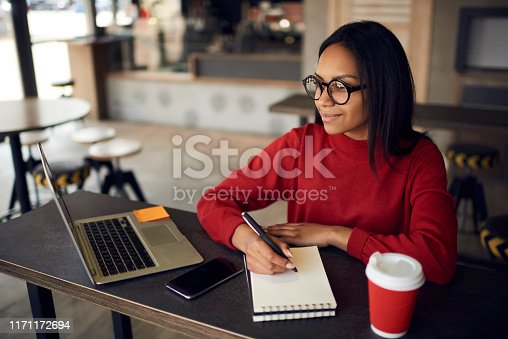 istock Positive dark skinned hipster girl in optical spectacles for vision correction looking away while creating new article with romantic idea in textbook for posting at own web blog via laptop device 1171172694