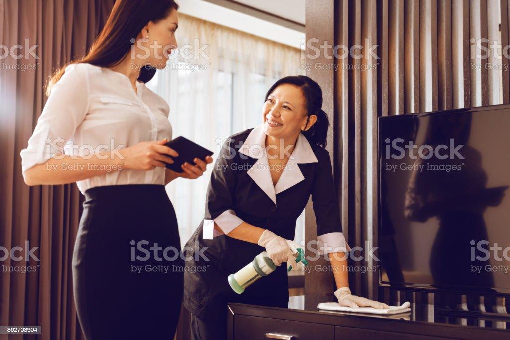 Positivo camarera encantada de lustrar muebles - foto de stock