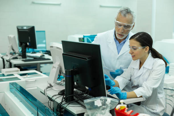 Positive delighted colleagues working at their project Technical research. Serious mature scientist wearing protective glasses while working in laboratory microbiologist stock pictures, royalty-free photos & images