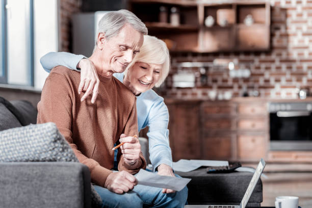positive delighted couple staring at computer - social security check stock photos and pictures